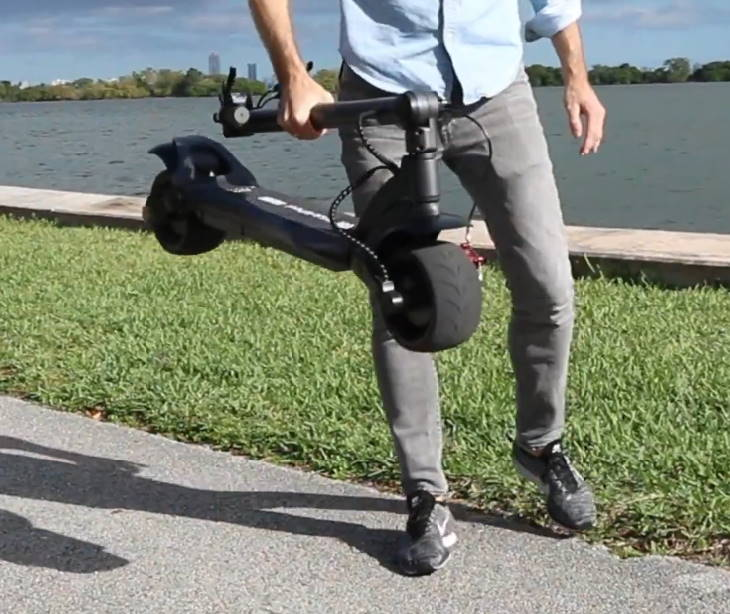 person carrying a folded Mercane WideWheel Pro