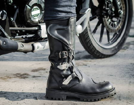 person wearing motorcycle boots against a motorcycle