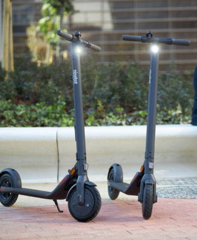 two Ninebot E22E scooters with their lights on