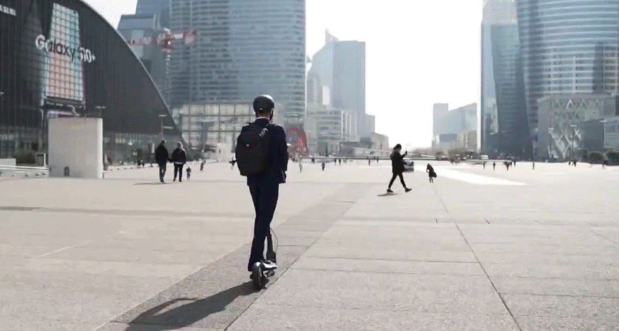 person riding a Ninebot Max electric scooter in an urban setting
