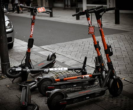 several Spin rental electric scooters on a sidewalk