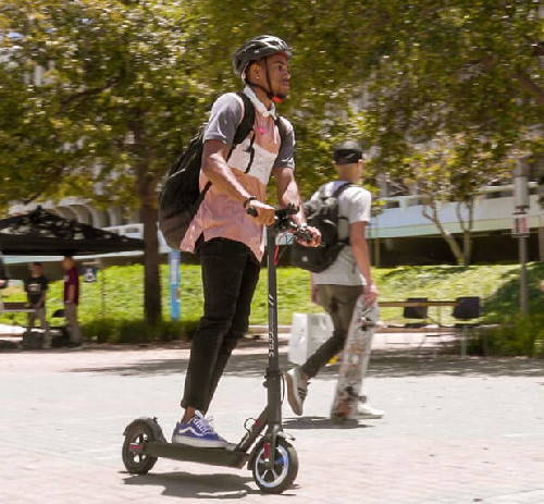 student with a backpack on an electric scooter