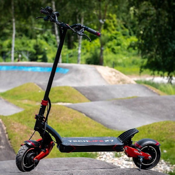 side view of a black Techlife X7S electric scooter with red details leaning on a stand in a riding park