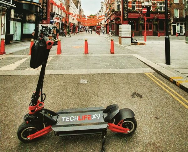 side view of the Techlife X9 electric scooter leaning on its stand in a city street