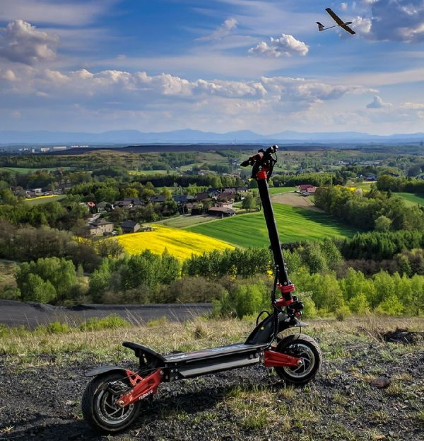 Techlife X9 electric scooter climbed on a hill overlooking green fields and blue skies