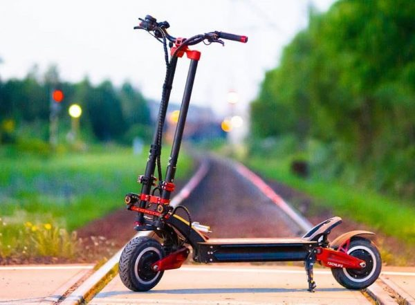 side view of the Techlife X9 electric scooter leaning on its stand standing on a railroad