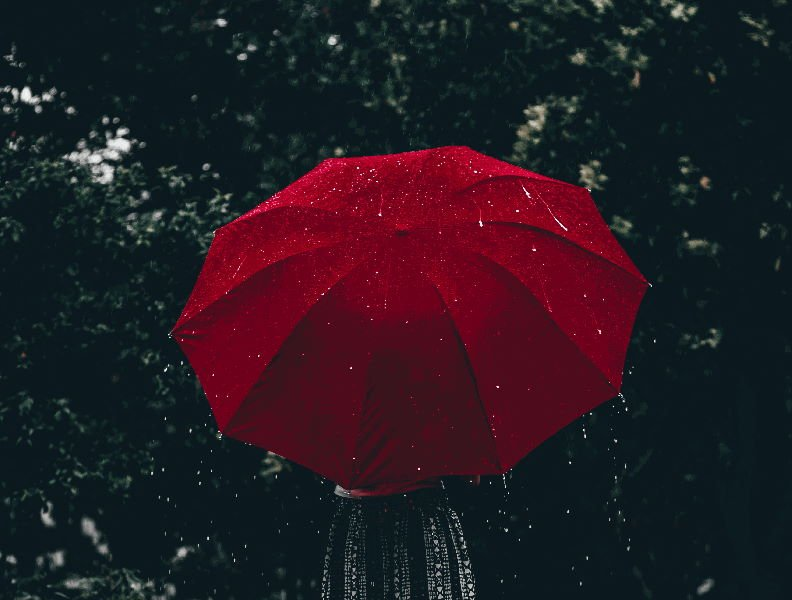 person under red waterproof umbrella protected from rain