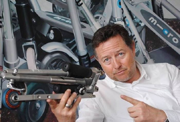 Wim Outober, inventor of the modern kick scooter, holding a Micro scooter